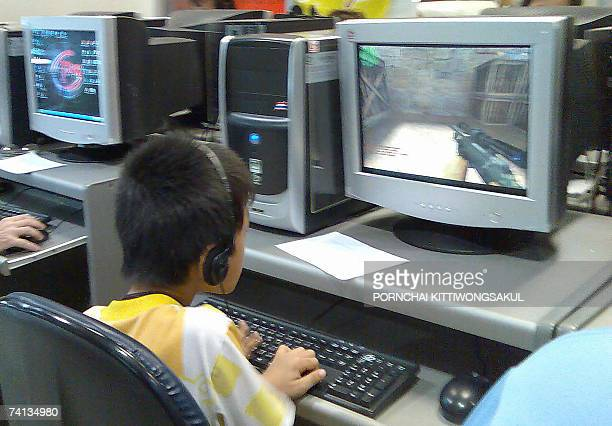 A Thai child enjoys playing a computer game at a game shop in Bangkok 29 April 2007 'Addiction to online games is among the top nine reasons for poor...