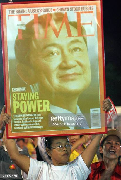 A Thai protester holds a portrait of former prime minister Thaksin Shinawatra when he appeared on the cover of Time Magazine during a demonstration...