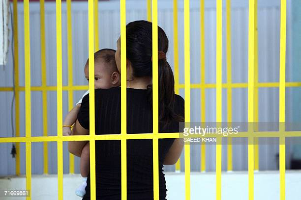 An unidentified woman with child waits at the detention center where US teacher John Mark Karr being held at the Thai Immigration Department in...
