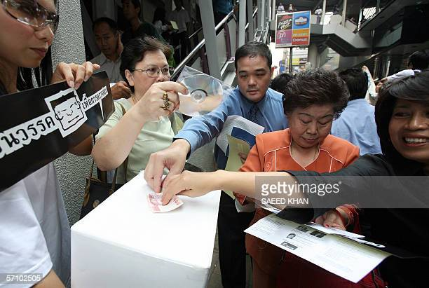 Bystanders drop donations in a box to fund the current antiThai Prime Minister Thaksin Shinawatra campaign at a protest organised by a section of...