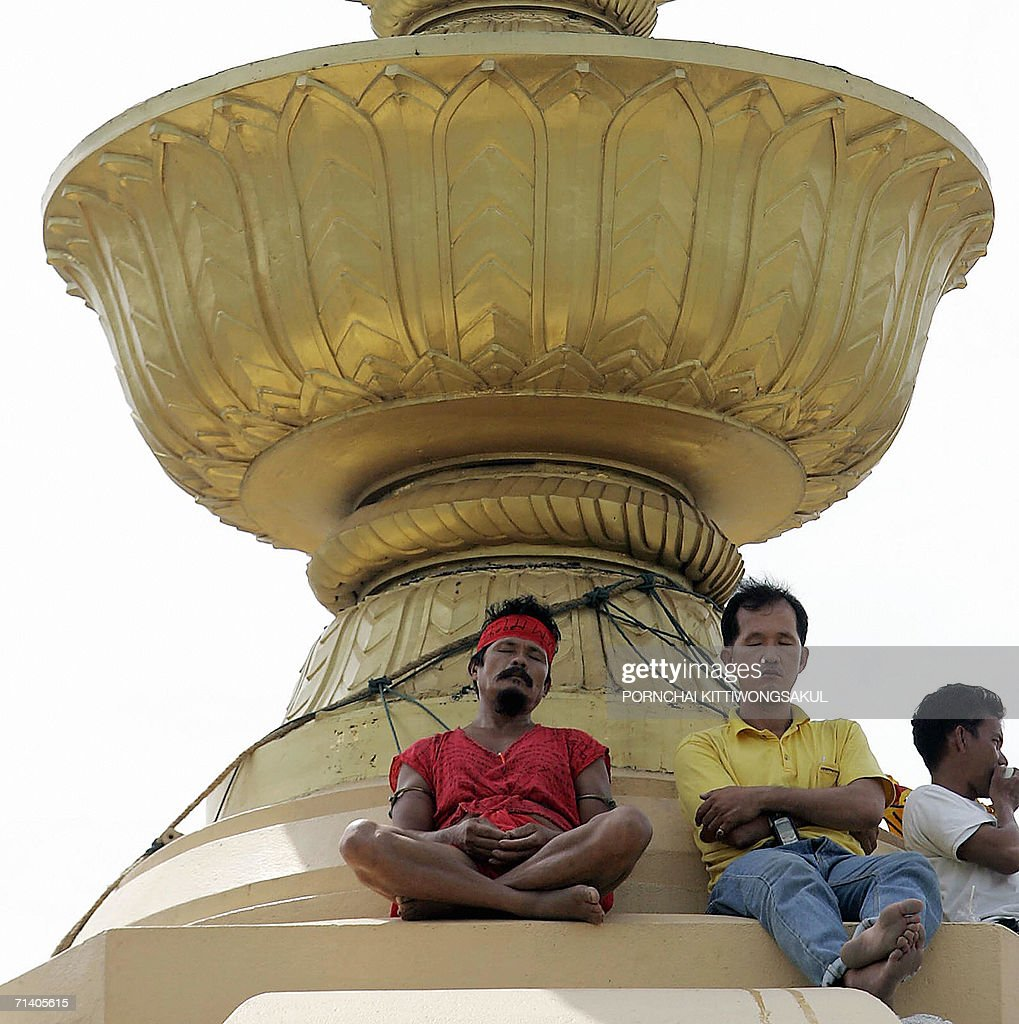 Members of a group called 'Democracy Dissemination' sit on the Democracy Monument during protest in Bangkok 10 July 2006 Three Thai protesters spent...