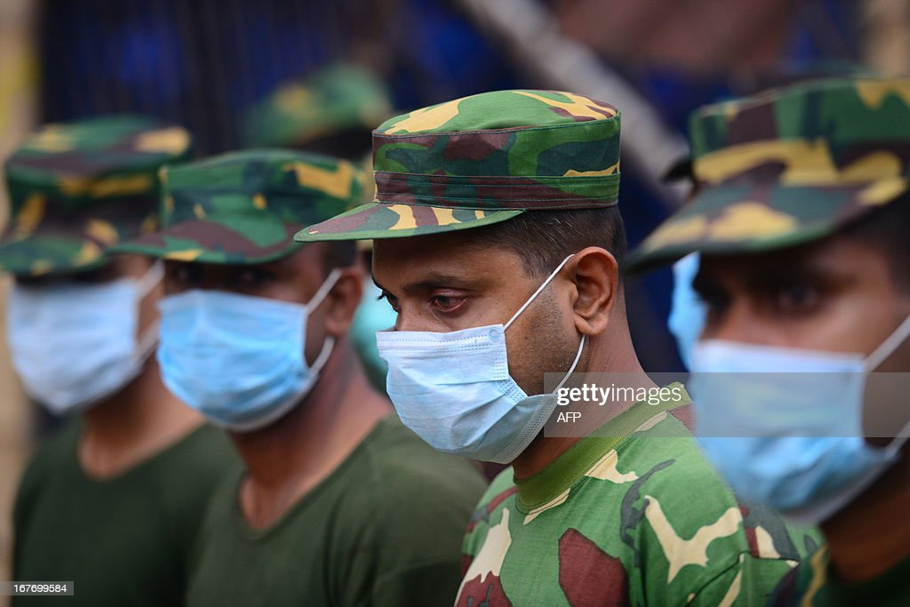 Bangladesh Army personal use masks to protect themselves from the smell of decaying bodies as they prepare to search the rubble of an eight-storey building that collapsed for survivors in Savar, on the outskirts of Dhaka on April 28, 2013. Four people were hauled out alive overnight more than 90 hours after the disaster, but the last feeble cries for help, still audible from inside the mountain of rubble early in the day, appeared to have ended. Rescue teams at the site of a collapsed factory block in Bangladesh where 363 people have died called in heavy-lifting equipment as hopes of finding more survivors faded. AFP PHOTO/ Munir uz ZAMAN