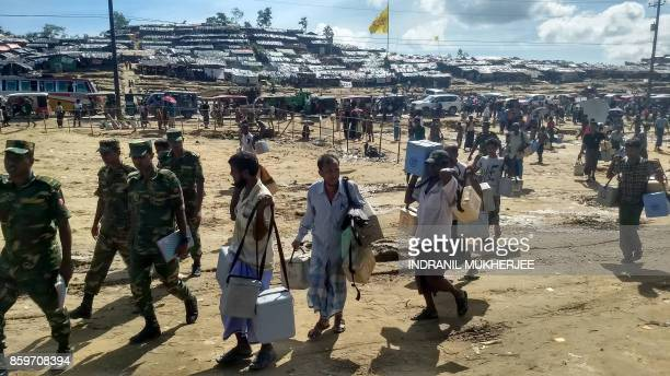 TOPSHOT Bangladesh army personel direct Rohingya volunteers carrying ice boxes with cholera vaccines at the Thangkhali refugee camp in Ukhia district...