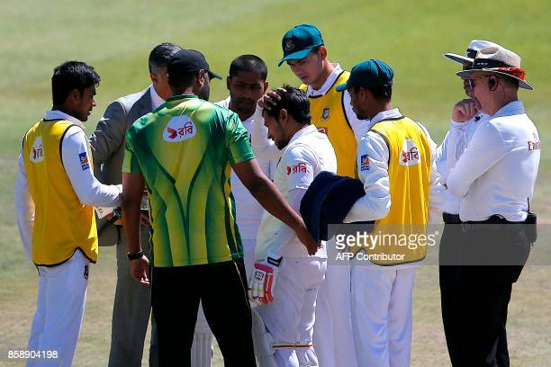 Bangladesh batsman Mushfiqur Rahim holds his head as he is attended by umpires medics and team members after he was hit on the head by a ball...