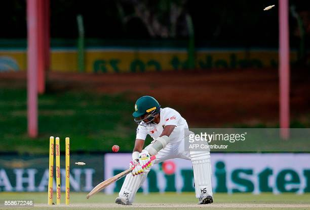 Bangladesh batsman Rubel Hossain looks back at his shattered stumps after his dismissal by South Africa's Kagiso Rabada during the second day of the...