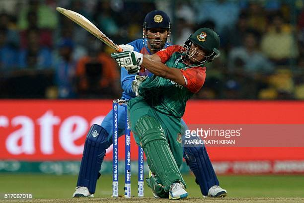 Bangladesh batsman Shakib AlHasan is watched by India's captain Mahendra Singh Dhoni as he plays a shot during the World T20 cricket tournament match...