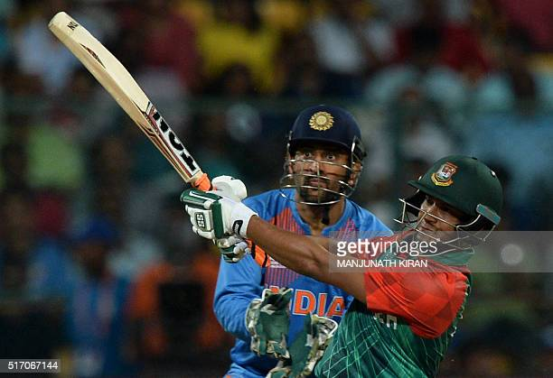 Bangladesh batsman Shakib AlHasanis watched by India's captain Mahendra Singh Dhoni as he plays a shot during the World T20 cricket tournament match...