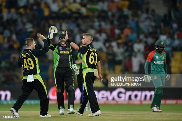 Bangladesh batsman Shuvagata Hom walks back to the pavilion while Australian bowler Adam Zampa celebrates his LBW during the World T20 cricket...