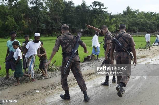 TOPSHOT Bangladesh Border Guard attempts to clear Rohingya Muslim refugees off a road near Balukhali refugee camp near the Bangladehsi district of...
