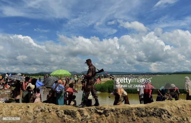 Bangladesh border guard walks amongst Rohingya refugees walking in an area near no man's land on the Bangladesh side of the border with Myanmar after...