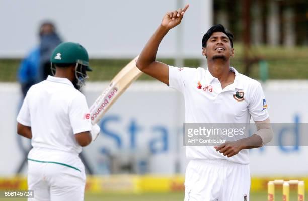 Bangladesh bowler Mustafizur Rahman celebrates the dismissal of unseen South African batsman Hashim Amla during the fourth day of the first Test...
