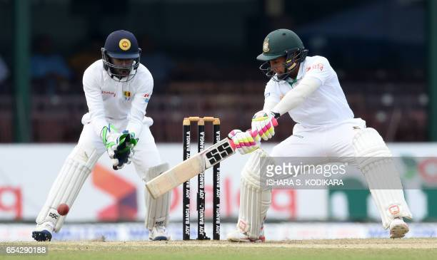 Bangladesh captain Mushfiqur Rahim plays a shot as Sri Lankan wicketkeeper Niroshan Dickwella looks on during the third day of the second and final...