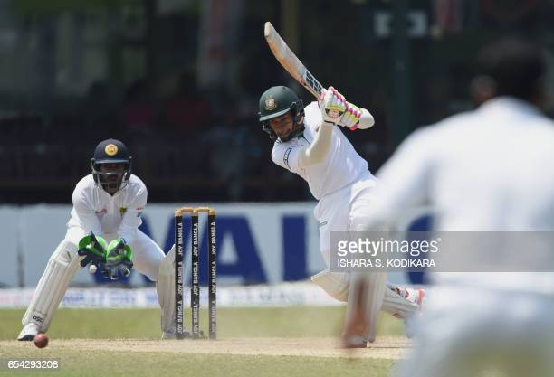 Bangladesh captain Mushfiqur Rahim plays a shot as Sri Lankan wicketkeeper Niroshan Dickwella looks onduring the third day of the second and final...