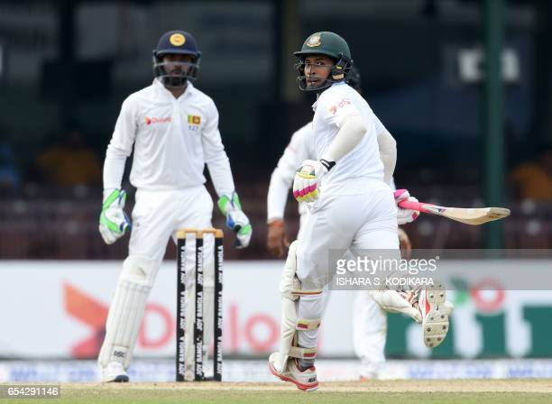 Bangladesh captain Mushfiqur Rahim run between the wickets as Sri Lankan wicketkeeper Niroshan Dickwella looks on during the third day of the second...