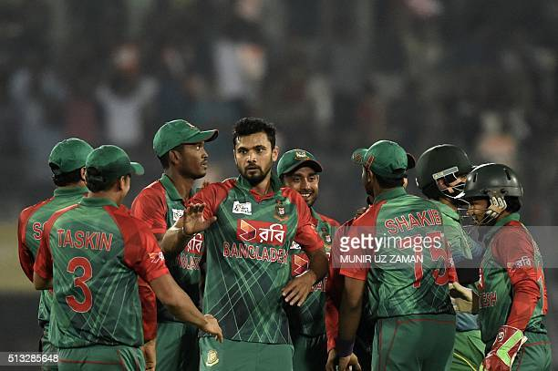 Bangladesh cricket captain Mashrafe Bin Mortaza celebrates with teammates after the dismissal of unseen Pakistan batsman Mohammad Hafeez during the...