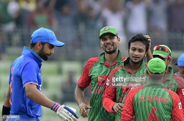 Bangladesh cricket captain Mashrafe Bin Mortaza congratulates teammate Shakib Al Hasan after the dismissal of Indian cricketer Virat Kohli during the...