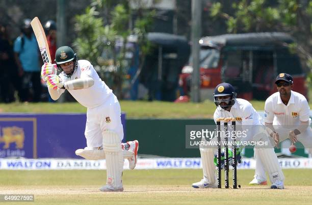 Bangladesh cricket captain Mushfiqur Rahim plays a shot as Sri Lanka wicketkeeper Niroshan Dickwella looks on during the third day of the opening...