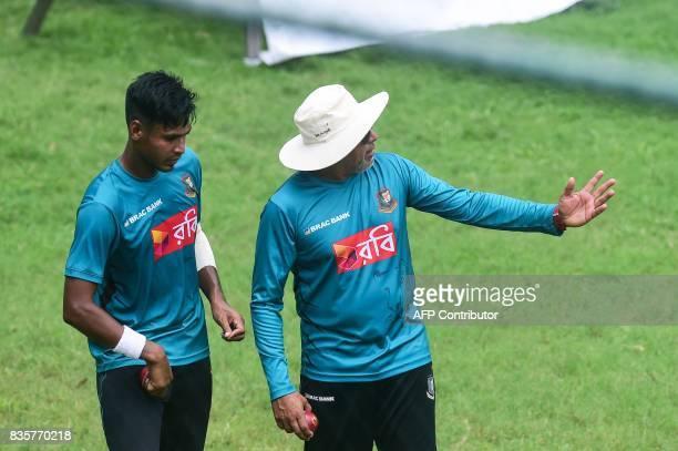 Bangladesh cricket coach Upul Chandika Hathurusingha talks to Bangladeshi cricketer Mustafizur Rahman during a training session at the ShereBangla...