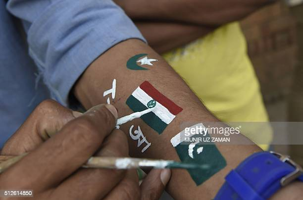 A Bangladesh cricket spectator paints the national flags of India and Pakistan onto his arm ahead of the match between the two countries at the Asia...