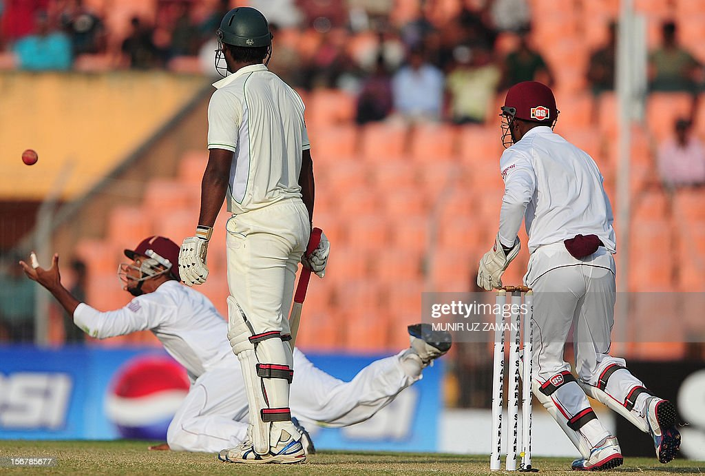 Bangladesh cricketer Abul Hasan (C) looks on as the West Indies cricketer Kieran Powell (L) tries to catch a ball during the first day of the second cricket Test match between Bangladesh and The West Indies at the Sheikh Abu Naser Stadium in Khulna on November 21, 2012. AFP PHOTO/ Munir uz ZAMAN