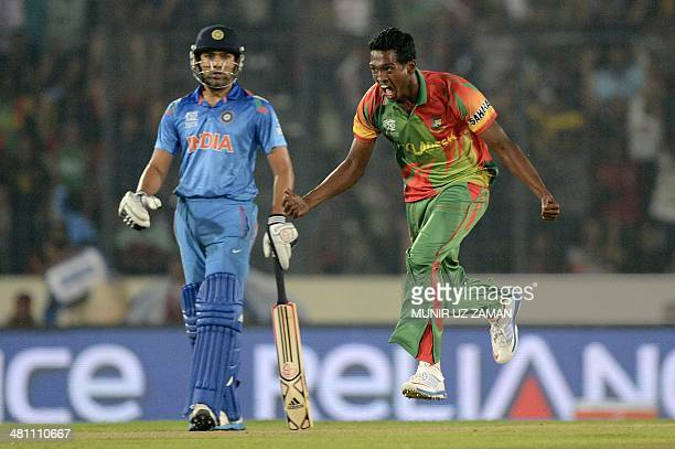 Bangladesh cricketer AlAmin Hossain celebrates the dismissal of Indian cricketer Shikhar Dhawan as Indian cricketer Rohit Sharma looks on during the...