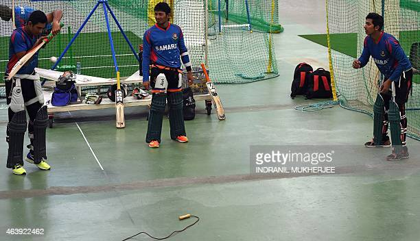 Bangladesh cricketer Anamul Haque looks on as teammate Mohammad Mahmadulla gets some throwdowns from compatriot Soumya Sarkar during an indoor...