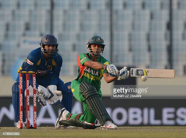 Bangladesh cricketer Arafat Sunny plays a shot as the Sri Lankan wicketkeeper Kumar Sangakkara looks on during the tenth match of the Asia Cup oneday...