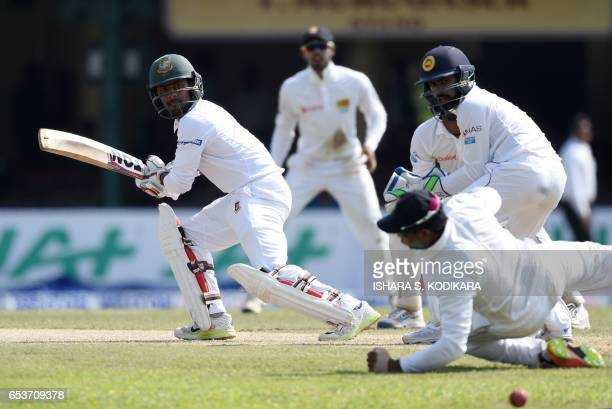 Bangladesh cricketer Imrul Kayes plays a shot as Sri Lankan wicketkeeper Niroshan Dickwella watches the ball go past a fielder during the second day...