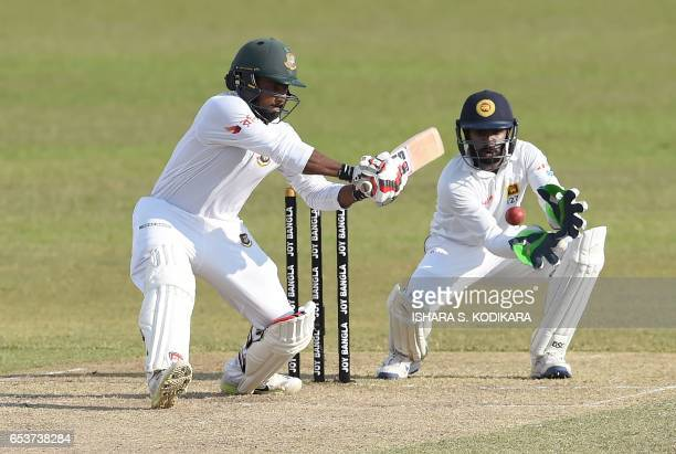 Bangladesh cricketer Imrul Kayes plays a shot as Sri Lankan wicketkeeper Niroshan Dickwella looks on during the second day of the second and final...
