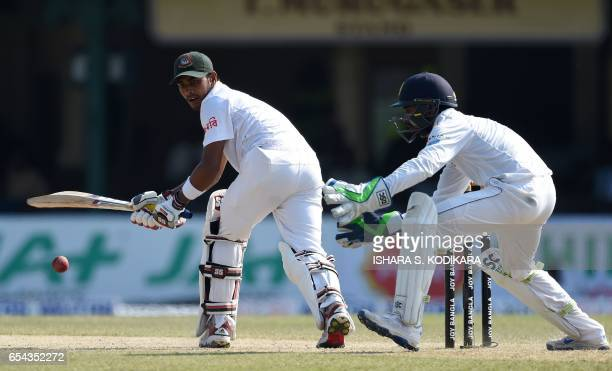 Bangladesh cricketer Mehedi Hasan plays a shot as Sri Lankan wicketkeeper Niroshan Dickwella looks on during the third day of the second and final...