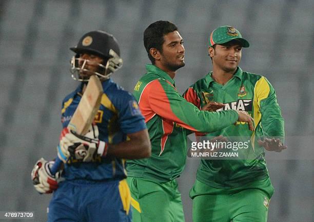 Bangladesh cricketer Mohammad Mahmudullah celebrates with his teammate Shakib Al Hasan after the dismissal of Sri Lankan cricketer Chaturanga de...
