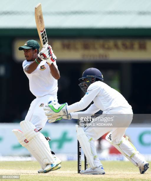 Bangladesh cricketer Mosaddek Hossain plays a shot as Sri Lankan wicketkeeper Niroshan Dickwella looks on during the third day of the second and...