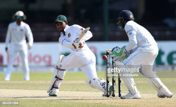 Bangladesh cricketer Mosaddek Hossain plays a shot past Sri Lankan wicketkeeper Niroshan Dickwella during the third day of the second and final Test...