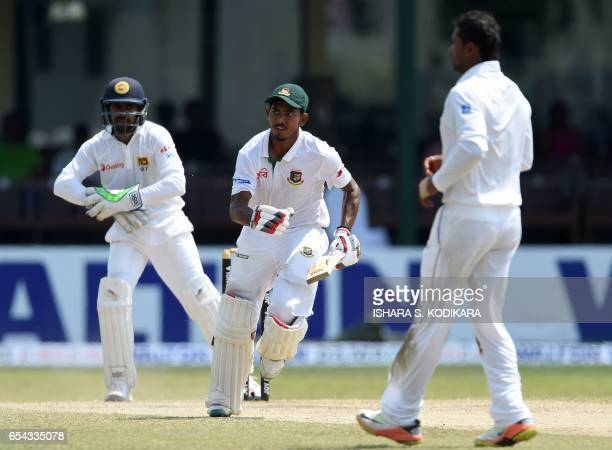 Bangladesh cricketer Mosaddek Hossain runs between the wickets as Sri Lankan wicketkeeper Niroshan Dickwella looks onduring the third day of the...
