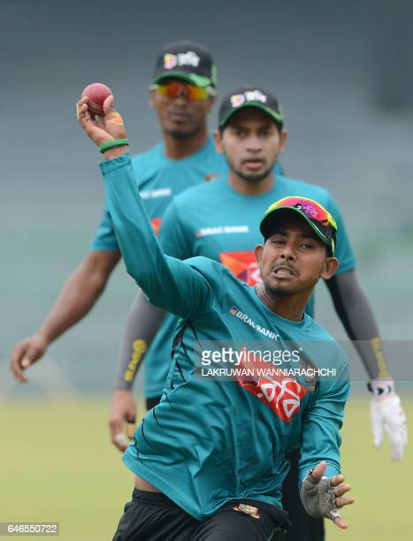 Bangladesh cricketer Mosaddek Hossain throws a ball as teammates look on during a practice session at the R Premadasa Stadium in Colombo on March 1...
