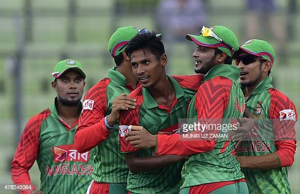 Bangladesh cricketer Mustafizur Rahman celebrates with teammate Shakib Al Hasan and others after the dismissal of unseen Indian batsman Rohit Sharma...