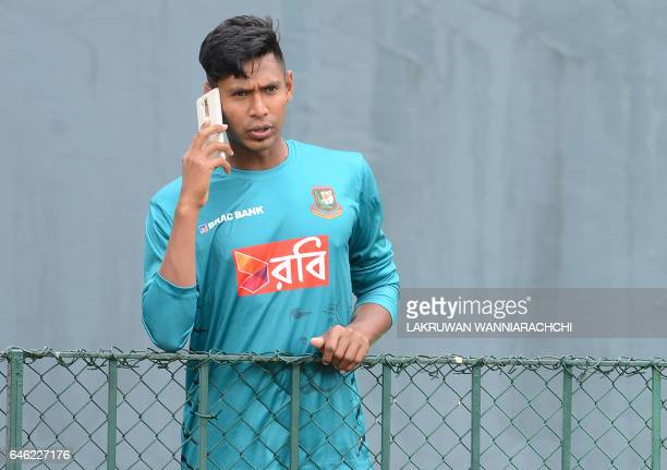 Bangladesh cricketer Mustafizur Rahman speaks on the phone during a practice session at The R Premadasa Stadium in Colombo on February 28 ahead of a...