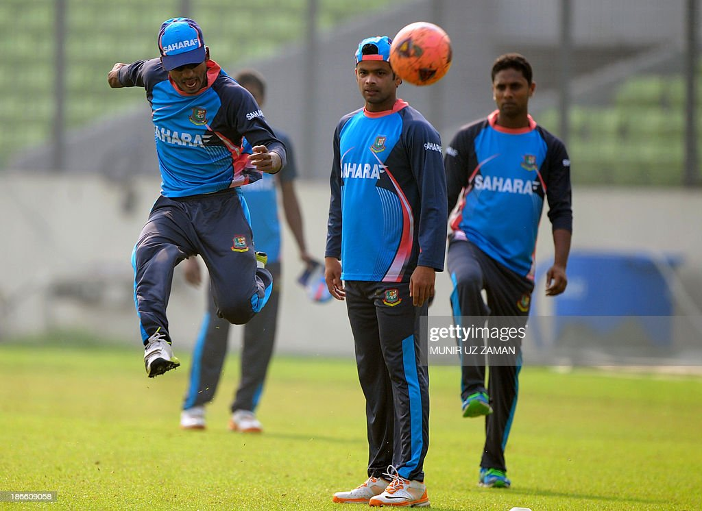 Bangladesh cricketer Naeem Islam (L) plays with a football as teammates Abdur Razzak (2R) and Sohag Gazi look on during a training session at the Sher-e Bangla National Stadium in Dhaka on November 2, 2013, in preparation for the third One Day International (ODI) cricket match against New Zealand to be played on November 3. AFP PHOTO/ Munir uz ZAMAN