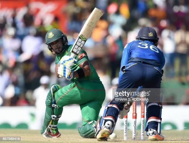 Bangladesh cricketer Sabbir Rahman plays a shot as Sri Lankan wicketkeeper Dinesh Chandimal looks on during the first one day international cricket...