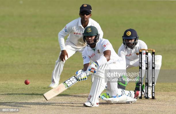 Bangladesh cricketer Sabbir Rahman plays a shot as Sri Lankan wicketkeeper Niroshan Dickwella looks on during the second day of the second and final...