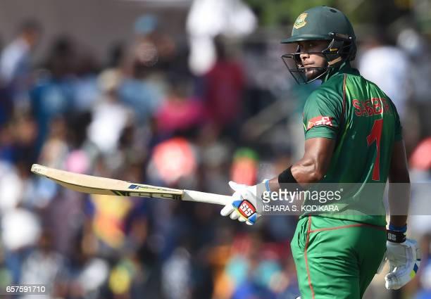 Bangladesh cricketer Sabbir Rahman raises his bat to the crowd after scoring a halfcentury during the first one day international cricket match...