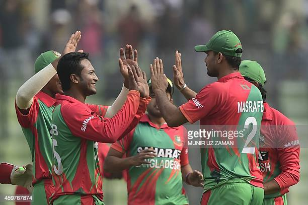 Bangladesh cricketer Shakib Al Hasan celebrates with his captain Mashrafe Bin Mortaza after the dismissal of the Zimbabwe cricketer Vusi Sibanda...