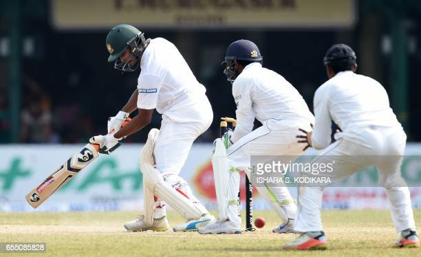 Bangladesh cricketer Shakib Al Hasan is watched by Sri Lankan wicketkeeper Niroshan Dickwella as he reacts after being bowled out by unseen Sri...