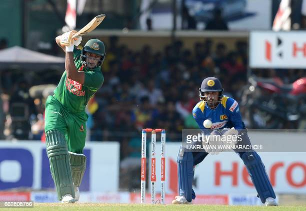 Bangladesh cricketer Shakib Al Hasan is watched by Sri Lankan wicketkeeper Dinesh Chandimal as he plays a shot during the third and final one day...