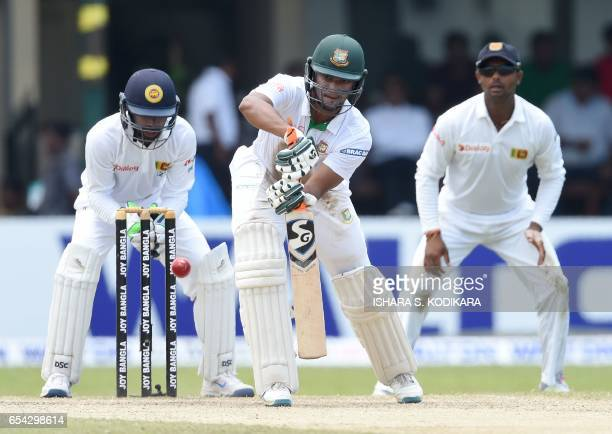 Bangladesh cricketer Shakib Al Hasan plays a shot as Sri Lankan wicketkeeper Niroshan Dickwella looks on during the third day of the second and final...