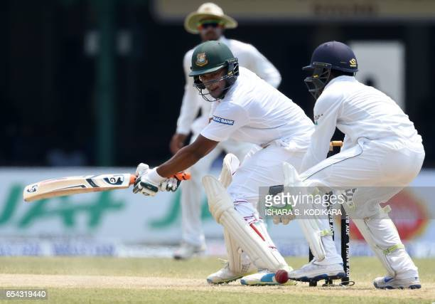 Bangladesh cricketer Shakib Al Hasan plays a shot past Sri Lankan wicketkeeper Niroshan Dickwella during the third day of the second and final Test...
