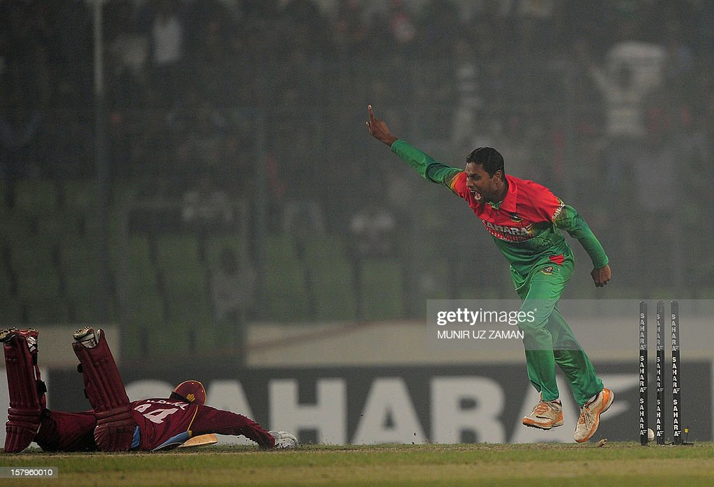 Bangladesh cricketer Sohag Gazi (R) reacts after the dismissal of the unseen West Indies batsman Veerasammy Permaul (L) during the fifth one day international between Bangladesh and West Indies at The Sher-e-Bangla National Cricket Stadium in Dhaka on December 8, 2012. AFP PHOTO/ Munir uz ZAMAN