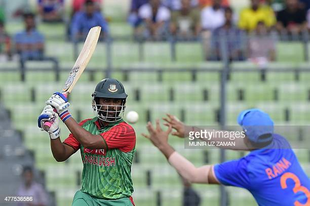 Bangladesh cricketer Tamim Iqbal plays a shot as Indian cricketer Suresh Raina tries to catch the ball during the first one day international cricket...