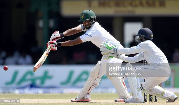 Bangladesh cricketer Tamim Iqbal plays a shot as Sri Lankan wicketkeeper Niroshan Dickwella looks on during the second day of the second and final...