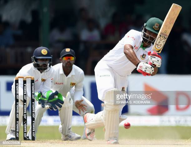 Bangladesh cricketer Tamim Iqbal plays a shot as Sri Lankan wicketkeeper Niroshan Dickwella looks on during the fifth and final day of the second and...